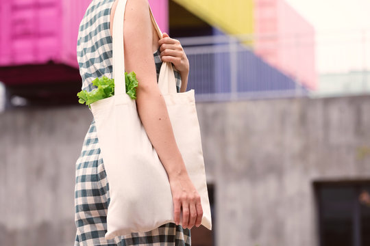 Eco bag in woman hands. Environment concept. Reusable eco bag. White tote bag canvas fabric with fresh food.