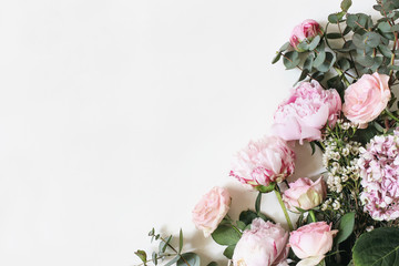 Feminine styled stock photo with pink roses, hydrangea, peony, flowers and eucalyptus leaves and branches isolated on white background. Flat lay, top view. Floral frame, botany decorative corner.