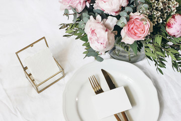 Feminine wedding, birthday mock-up scene. Porcelain plate, blank paper greeting card, golden box and cutlery. Beautiful bouquet of eucalyptus, pink roses and peony flowers. White table background.