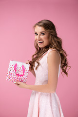 Surprised woman opening gift bag on the pink background