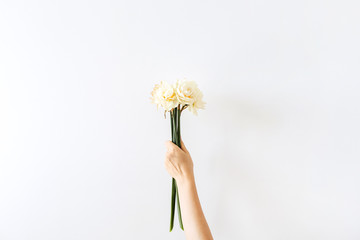 Poster Narcisse Female hand hold narcissus flowers bouquet on white background. Flat lay, top view minimal floral composition.