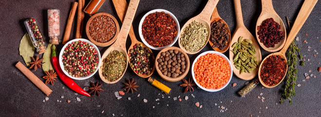 A set of spices and herbs. Indian cuisine. Pepper, salt, paprika, basil and other on a dark background Papier Peint