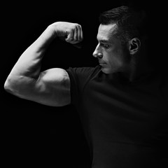 Strong man looking and showing her biceps arm on dark black background.