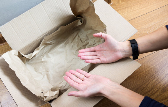 Female hands show an empty cardboard box only with packaging paper. E-commerce fraud, where is my order, concept image. Selective focus, close-up.