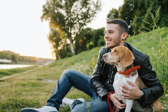 Young man sitting on the grass embraces the beloved dog at the park at sunset - Millennial in a moment of relaxation with his four-legged friend