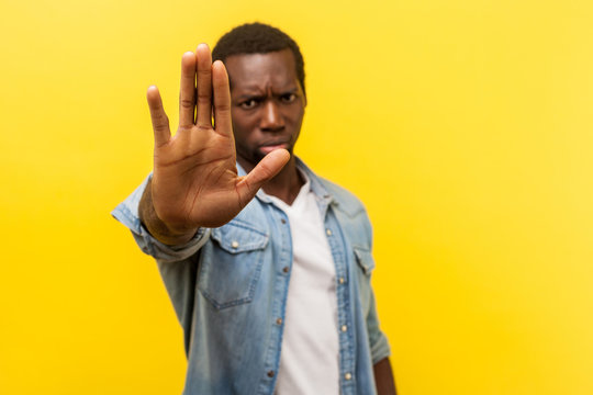 Prohibition. Portrait of serious angry man in denim casual shirt frowning showing stop gesture with palm of the hand, saying no, warning expression. indoor studio shot isolated on yellow background