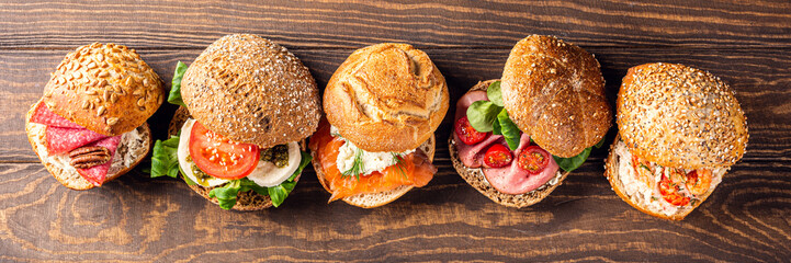 Assorted sandwiches on wooden background. Healthy food concept with copy space. Top view. Banner.