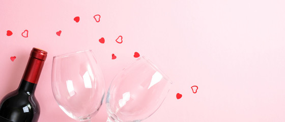 Valentines Day background with bottle of wine champagne, two glasses and heart shaped confetti on pink. Minimal flat lay style composition, top view. Valentines Day, romantic dinner couple concept