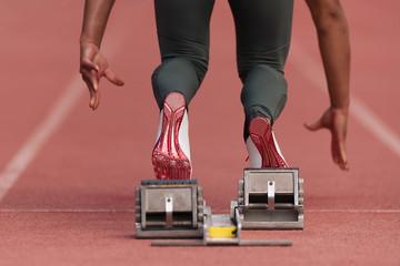 Fototapeta Back view of female feet on starting block ready for a sprint start obraz