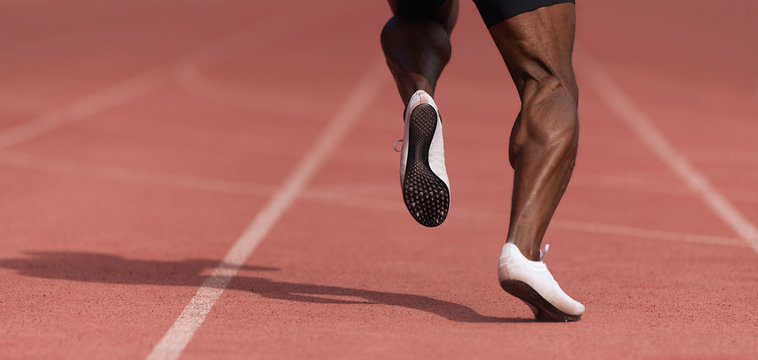 African-american male sportsman running on stadium track, dynamic run of sprinter in a stadium