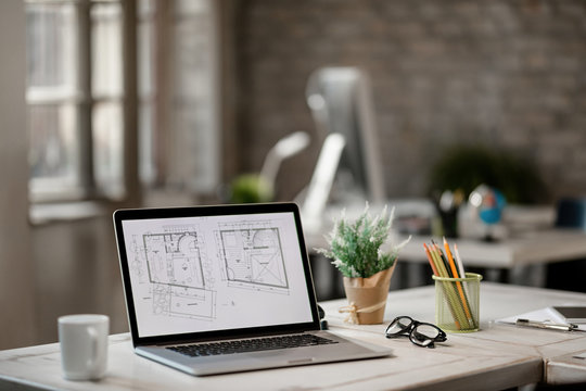 Blueprints on laptop monitor in real estate office.