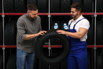 Mechanic helping client to choose car tire in auto store