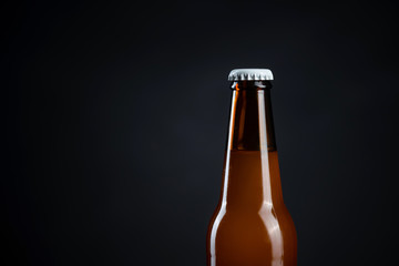 Cold unopened bottle of beer with cap on black background. Glass of refrigerated wheat or lager beer on dark background