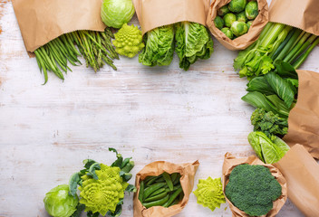 Healthy eating, copy space. Farmers market produce in paper bags. Green vegetables on white table, broccoli sprouts peas avocado courgette celery bok choy, top view, selective focus