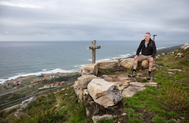 A hiker takes a break and sits high on a mountain on the Atlantic coast in Galicia in northern Spain. A stone cross stands in front of him. It is cloudy and you can see the coastline.