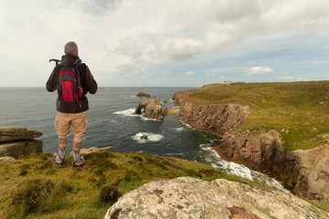 A hiker looks out to sea to the Lands End lighthouse in south-west England. The man stands with a backpack on the edge of the high cliffs. It's cloudy.