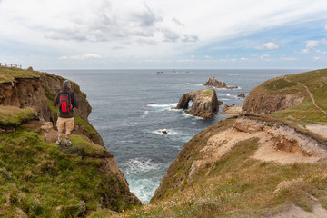 A hiker with a backpack and walking sticks looks out over the Atlantic at Lands End Lighthouse in south-west England. The man is standing on the edge of the cliff on the grass. It's cloudy.