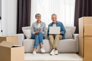 mature man with laptop and woman smiling at camera in new house