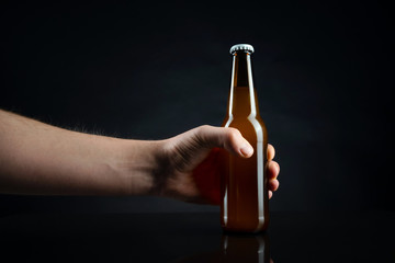 Men holding cold unopened bottle of beer with cap on black background. Hand holding glass of refrigerated wheat or lager beer on dark background