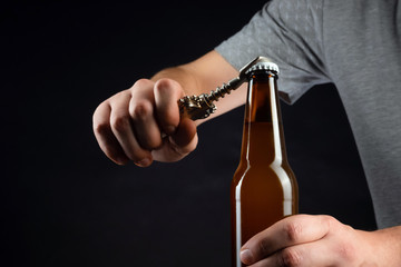 Men opening cold bottle of beer with cap on black background. Hands cracking refrigerated wheat or lager beer with an opener on dark background