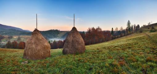Foto op Plexiglas Diepbruine haystack in the meadow. Dawn in the Carpathian mountains. picturesque morning