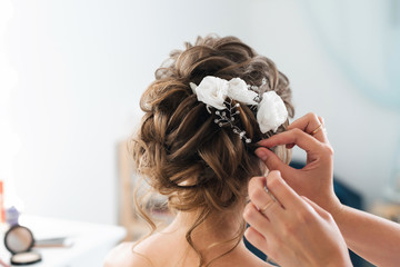 Tuinposter Kapsalon hairdresser makes an elegant hairstyle styling bride with white flowers in her hair
