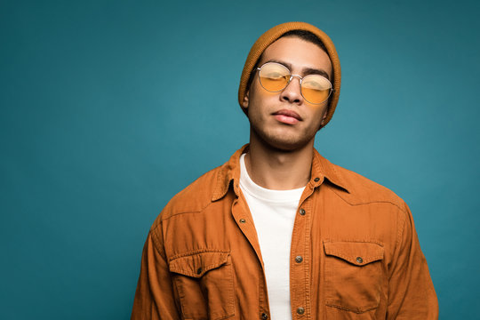 Photo of good-looking confident mixed race man in yellow outfit, wearing hat and glasses looking straight at camera, isolated over blue background