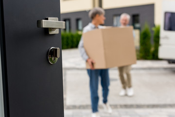 selective focus of door and mature man and woman bringing boxes to new house on background