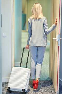 Businesswoman walking out of hotel room with suitcase