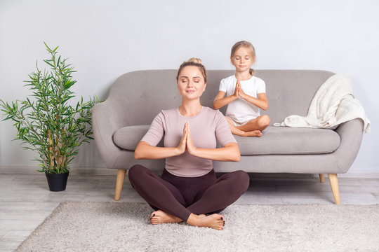Lotus posture. Young mother and little daughter with closed eyes and prayer gesture practicing yoga together at home, doing exercise breath technique, meditating in room, mindfulness and harmony