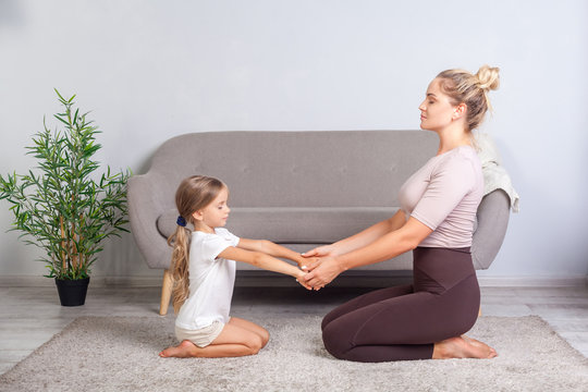 Young mother and little daughter keeping eyes closed sitting on floor, holding hands together and practicing yoga at home, doing exercise breath technique, meditating in room, mindfulness and harmony