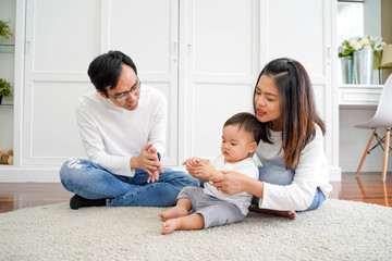 Happy Asian couple with infant son sitting on floor and clapping hands while playing and enjoying time together at home