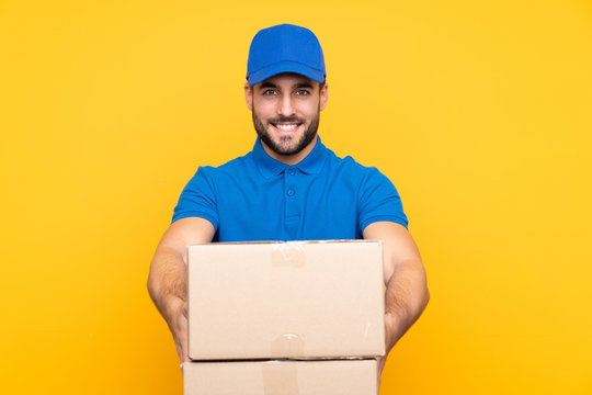 Delivery man over isolated yellow background with happy expression