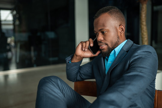 Corporate executive Black African businessman having serious conversation on mobile phone