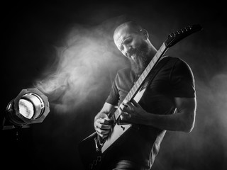 Bearded man playing guitar with spotlight
