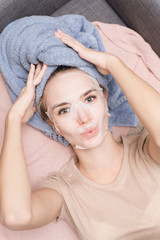 Cute lovely girl is lying on the couch in a disposable fabric moisturizing mask and towel on her...