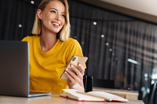 Photo of smiling blonde woman using laptop and smartphone while sitting