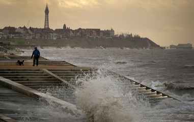 A man walks his dog in strong wind along the promenade near Blackpool, Britain