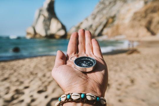 Man hand with compass symbolling adventure-seeking concept against Ursa beach, Sintra, Portugal