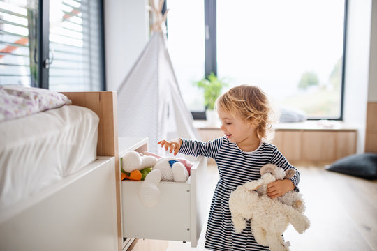 Cute small toddler girl indoors in bedroom playing.