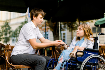 Pretty young woman on a wheelchair enjoying some good company on a date with her handsome man at a cafe outdoors in the city