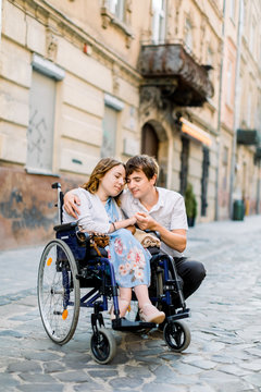 Young man hugs his pretty woman on the wheelchair, while walking together on the street of city. Couple in love in wheelchair embracing and touching foreheads with closed eyes, outdoors in the city