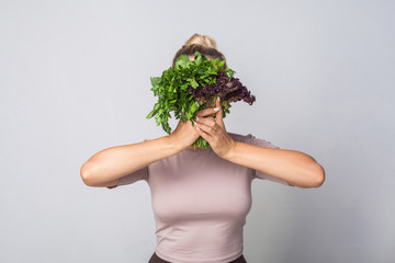 Young woman hiding face behind bunch of herbs, leafy green vegetables, holding parsley sorrel lettuce and smiling looking at camera, healthy nutrition, organic food. studio shot, grey background