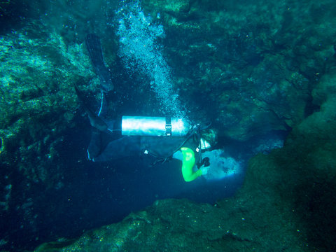 Underwater view of female scuba diver diving into cave.
