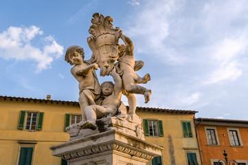 Putti fountain sculpture a sunset light. Pisa landmarks, Italy.