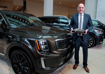 """Michael Cole, president of Kia Motors America, holds the trophy after winning the """"North American Utility Vehicle of the Year"""" for the 2020 Telluride vehicle in Detroit"""