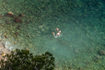 a group of young people swim in transparent water - Calanque of Sujiton