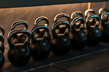 For you to choose. Stylish kettlebells weights made of black leather and iron lying in a row on the...