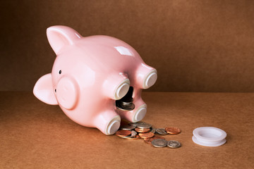 Piggy bank spilling out change onto counter