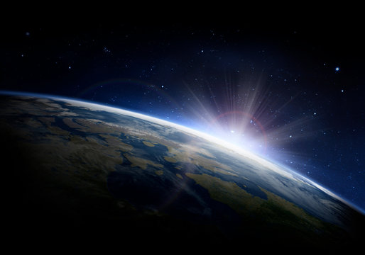 Sunlight ascending over Earth in outer space